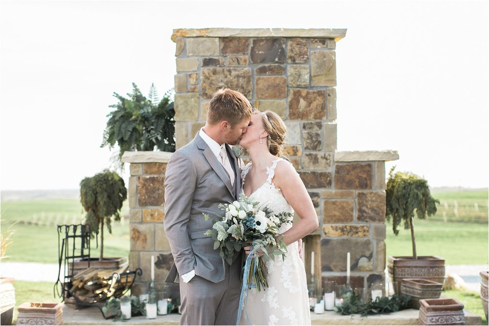 bride and groom kissing at fireplace ceremony alter