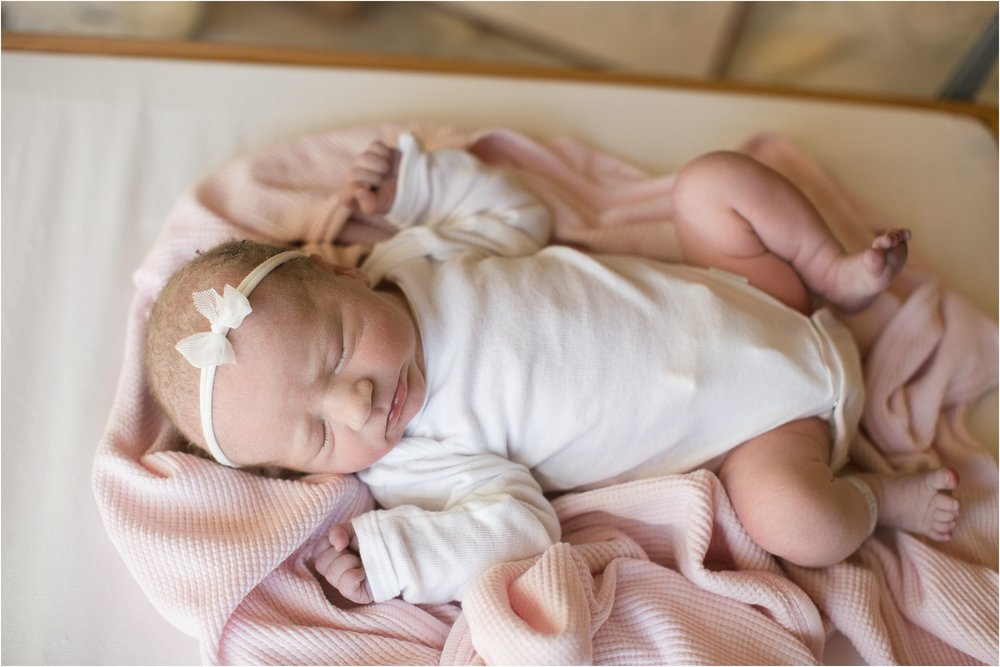 Newborn baby girl laying on a pink blanket in a white onesie hospital session