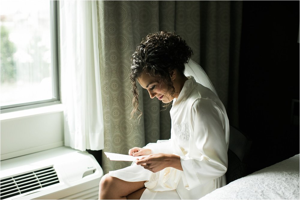 bride reading a letter by a window