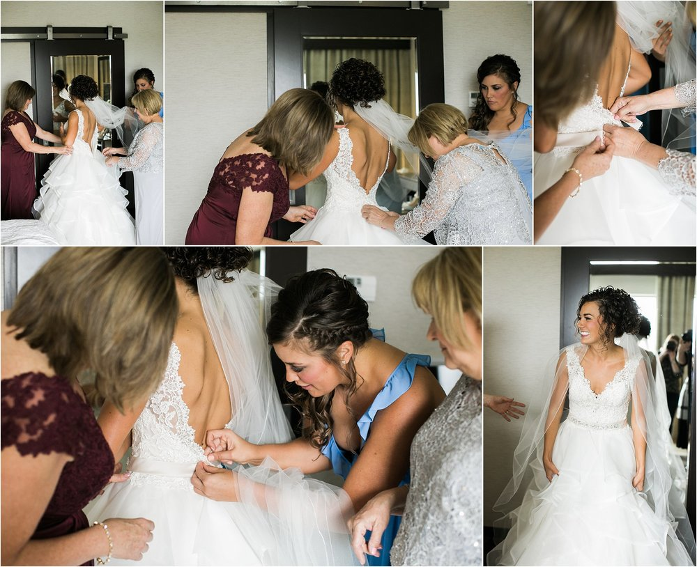 bride getting in her wedding dress with her mom