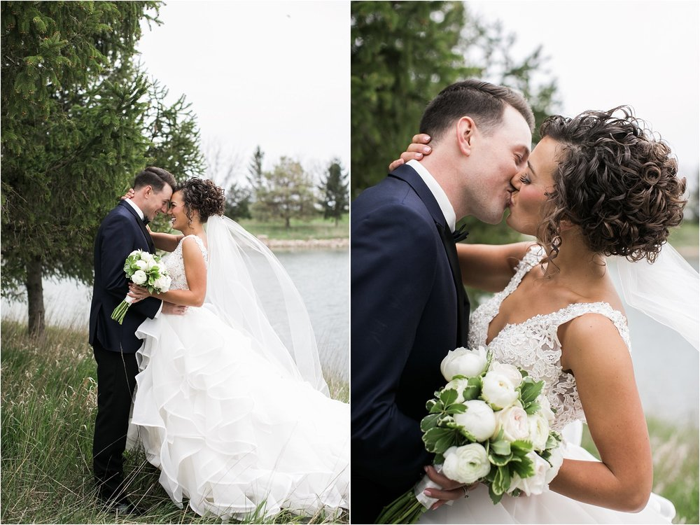bride and groom kissing in front of evergreen tree