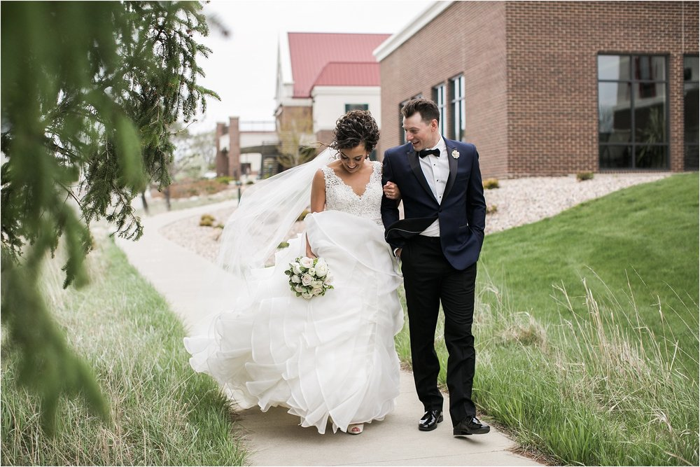 bride and groom laughing as they walk down path