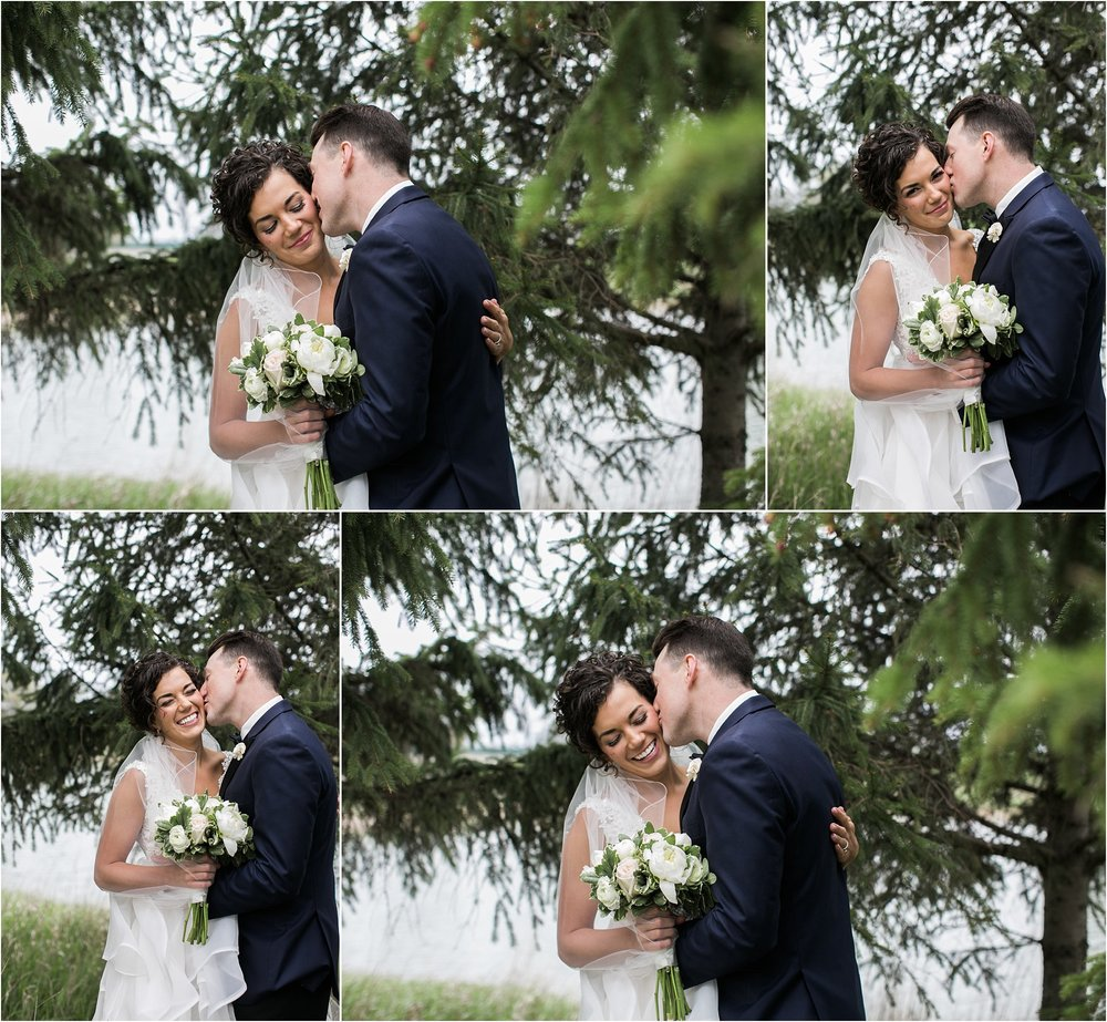 groom kissing his bride in front of evergreen tree