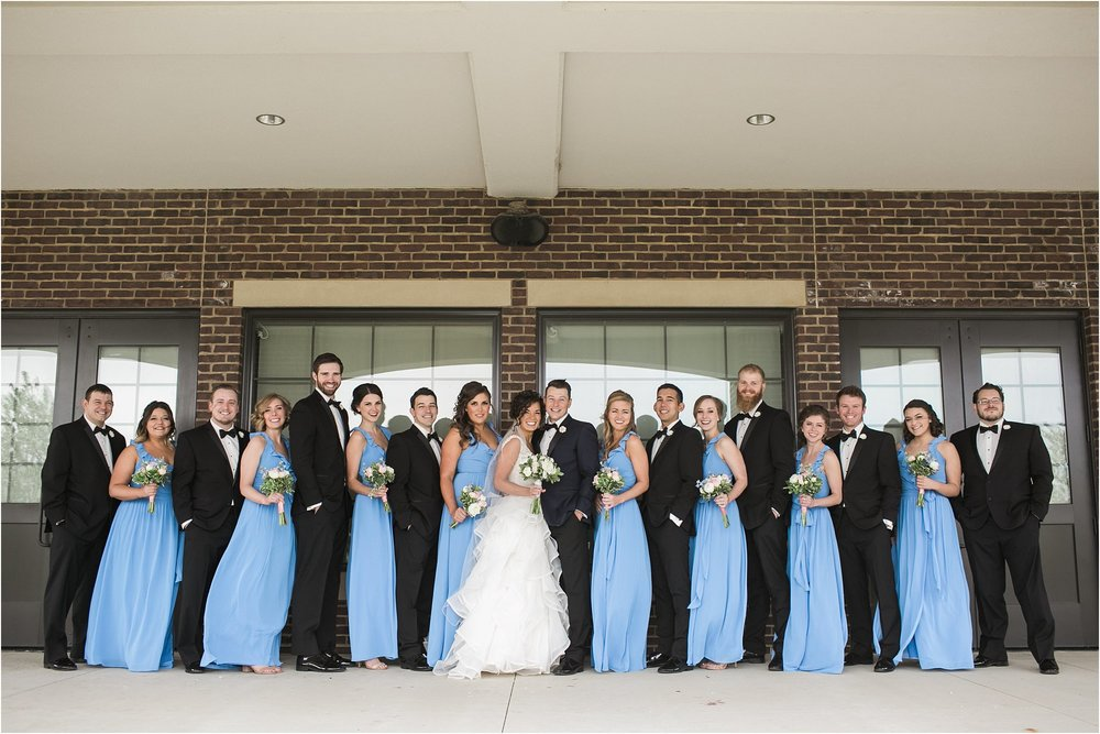bridal party in front of windows in cornflower blue dresses and black suits