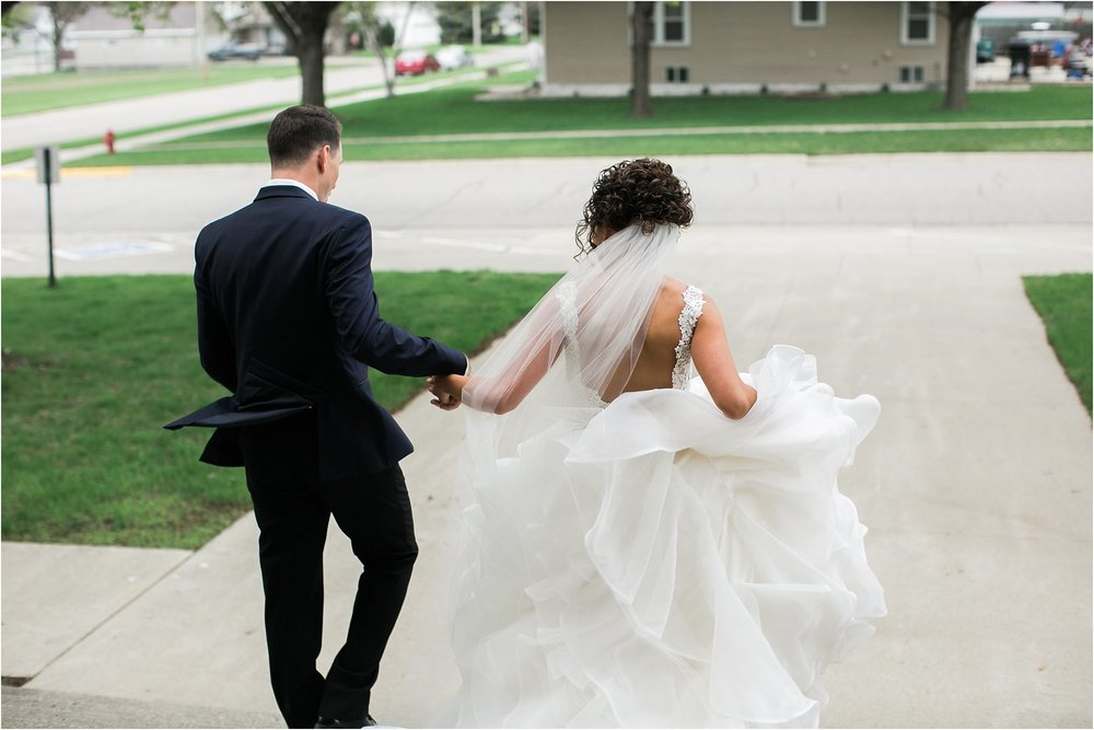 bride and groom exiting church holding hands
