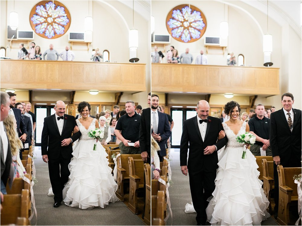 bride walking down the aisle with her dad in catholic church