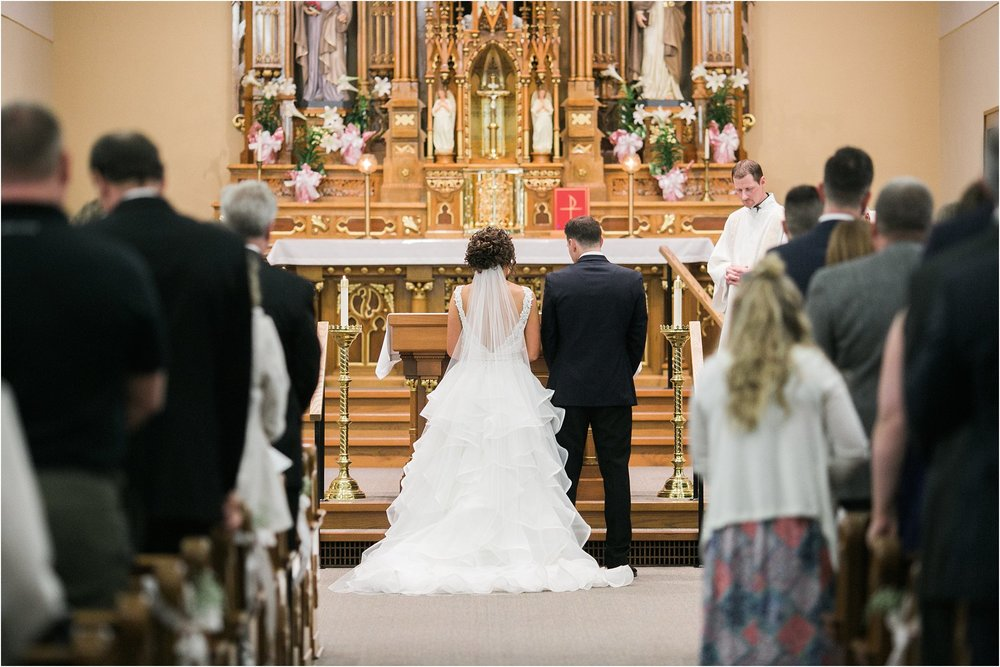 bride and groom standing at the front of a catholic church during mass