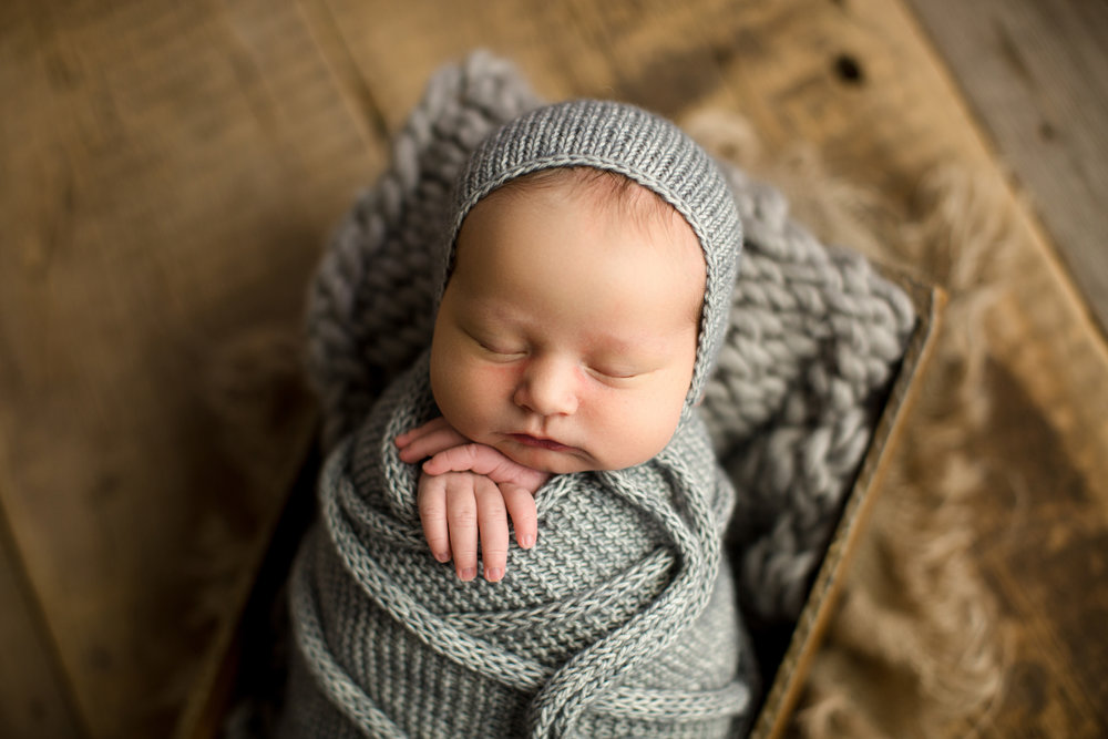 newborn baby with gray wrap and bonnet