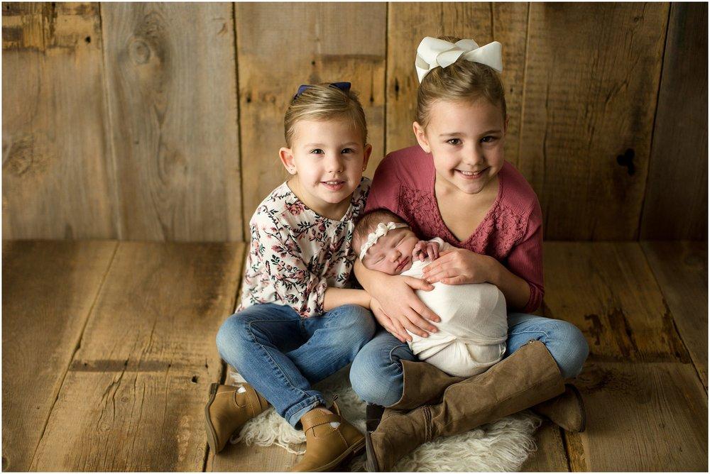 baby girl with big sisters on barnwood