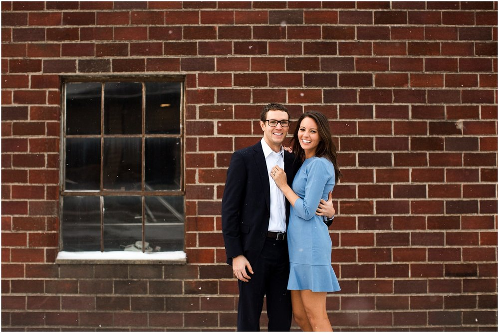 holly + chris snowy engagement session by brick wall