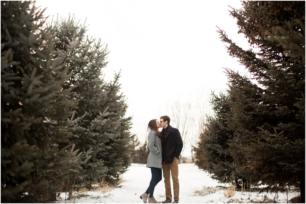 couple kissing between evergreen trees during winter