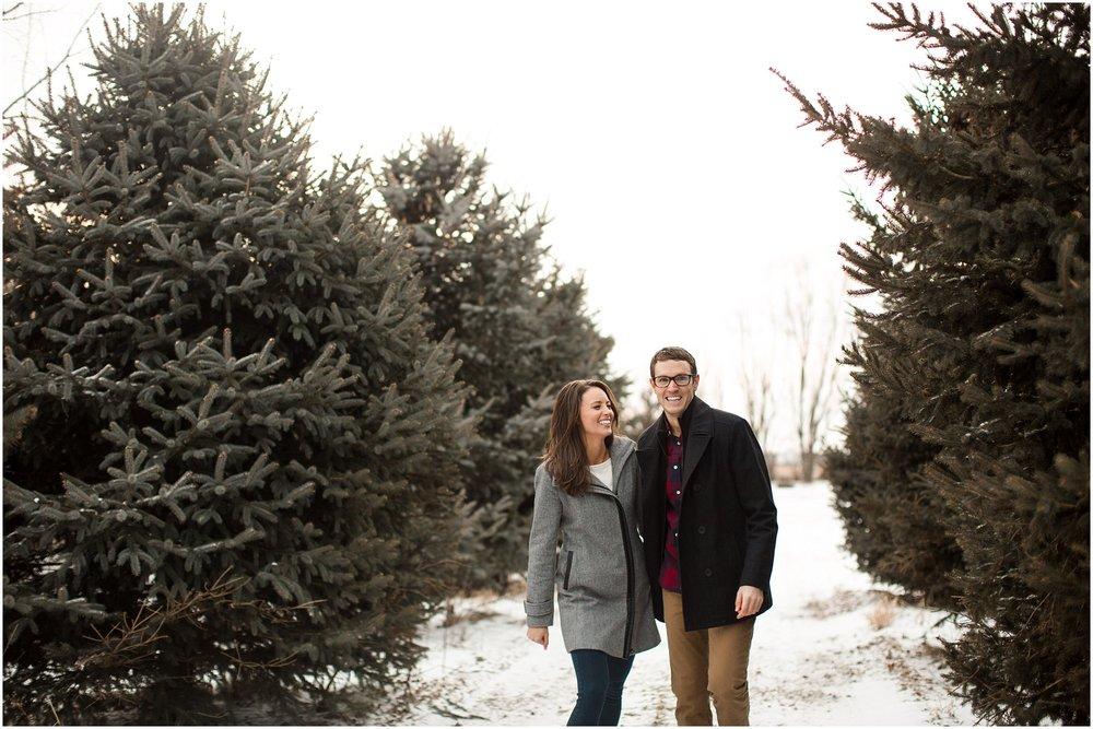 couple laughing walking between evergreens