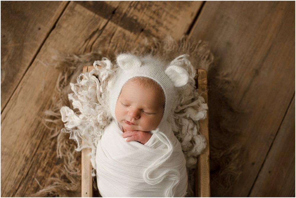 baby girl in a white bear bonnet