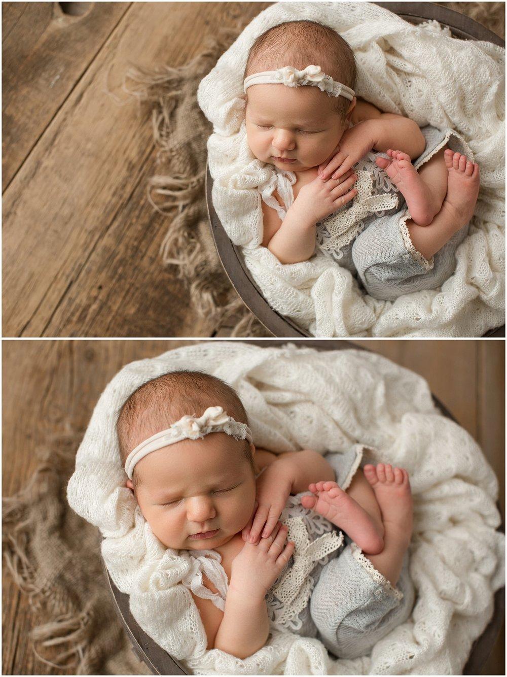 newborn girl wearing gray romper in a bowl