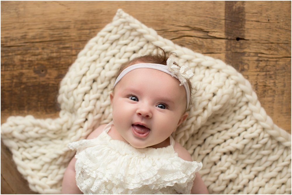 baby girl on knit layer smiling