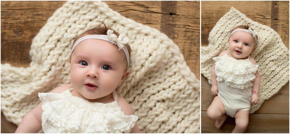 baby girl laying on barnwood backdrop with headband