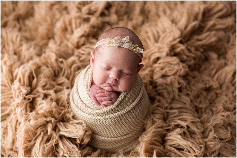 newborn girl on tan flokati rug with a smile