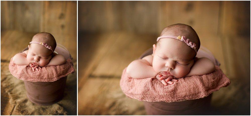 newborn girl in a mauve bucket
