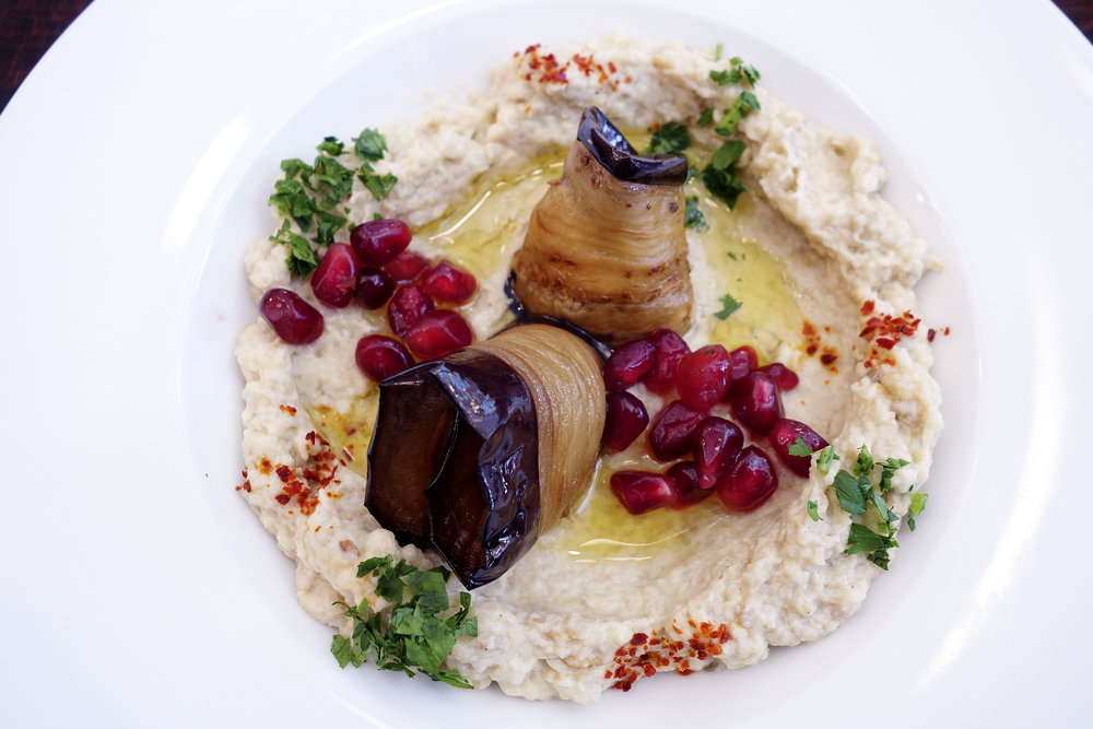 Hummus with pomegranate seeds and roasted eggplants.