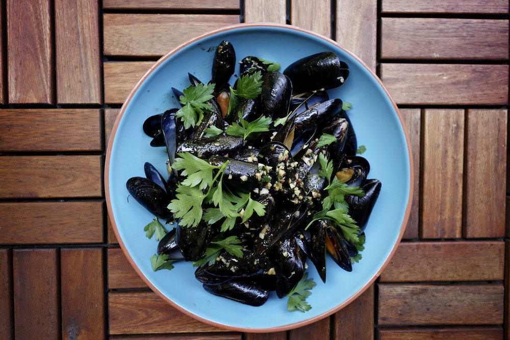 Mussels topped with parsley.