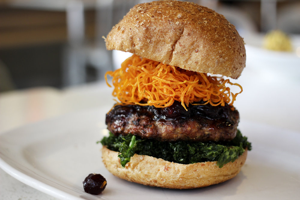 The Giving Bird   100% natural turkey topped with pomegranate molasses glaze, fried sweet potato strings, crispy kale, cranberry relish, whole wheat bun, and a housemade pomegranate bbq sauce.