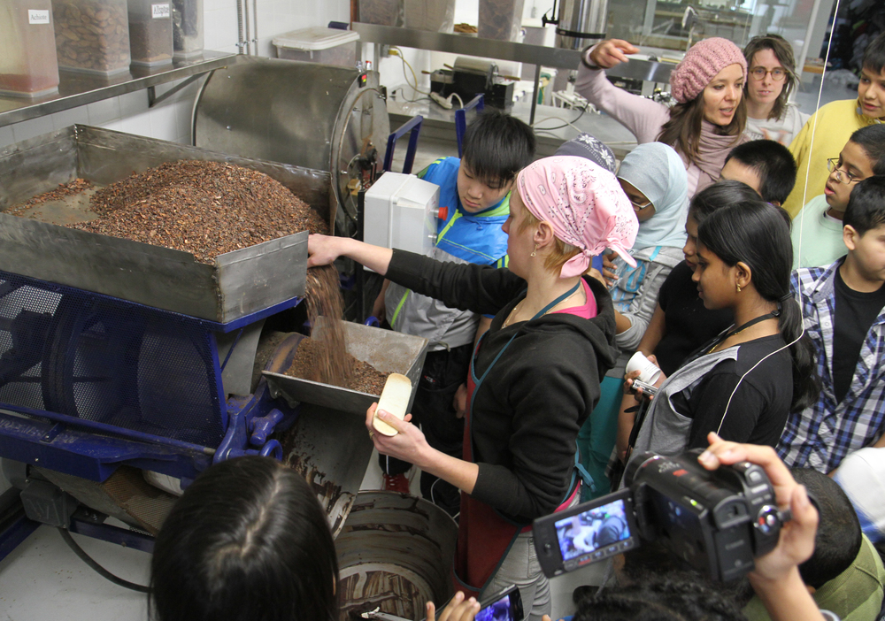 Ask Me Chocolates (2012), process/research image, artists and students witness the molino in action at Chocosol, a Toronto-based social enterprise producing small batch, horizontally-traded chocolate, image courtesy of The Pedagogical Impulse