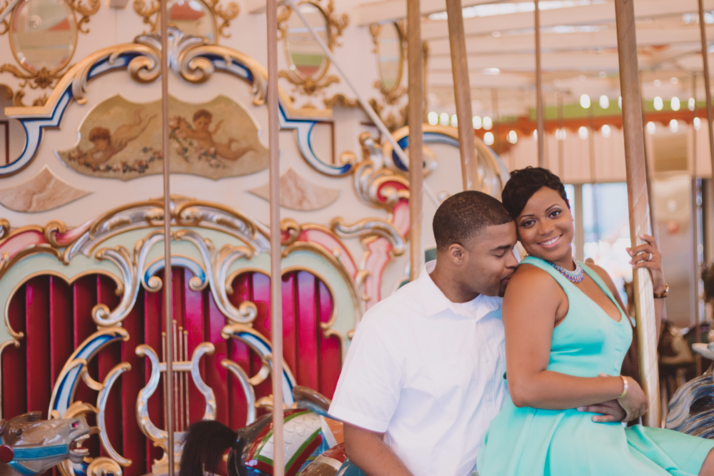 couple on merry go round during engagement photos