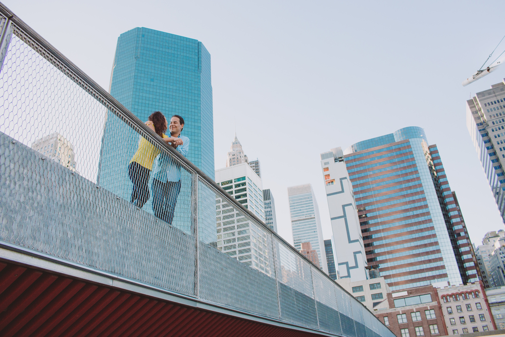 couple embracing on bridge in front of high rise buildings