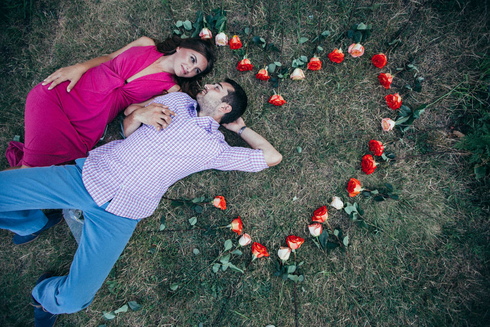 Couple laying in flower bed during park engagement
