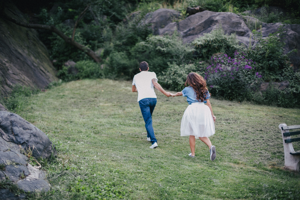 Couple running away together during engagement