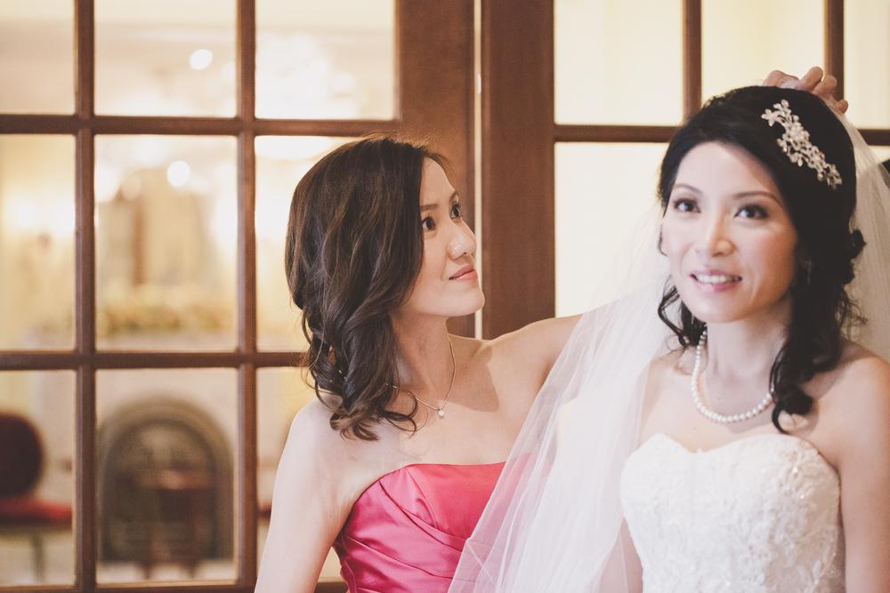 Sister bridesmaid helping bride get ready