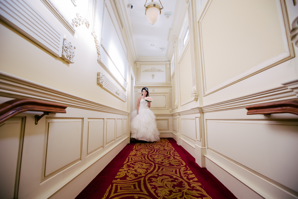 bride coming down the hallway in dress with bouquet