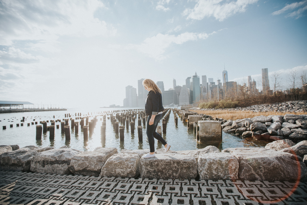 girl walking in front of nyc skyline