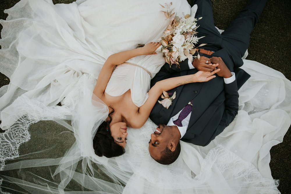 bride and groom laying on veil