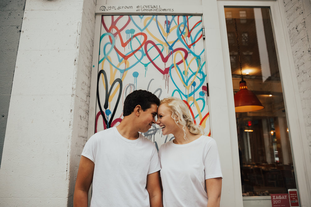 couple in front of love wall