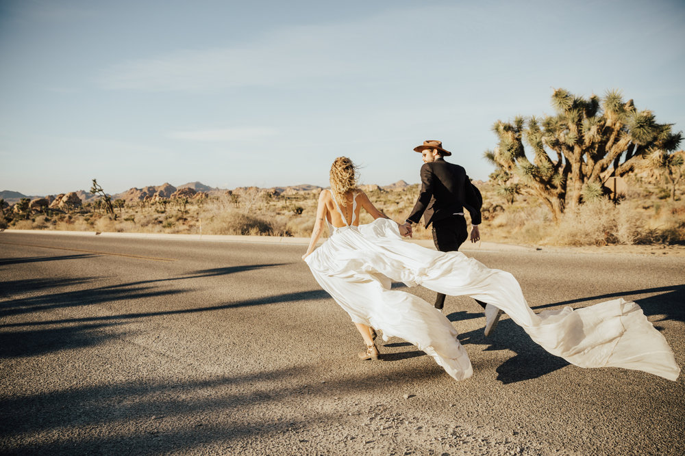 wedding couple running in street joshua tree