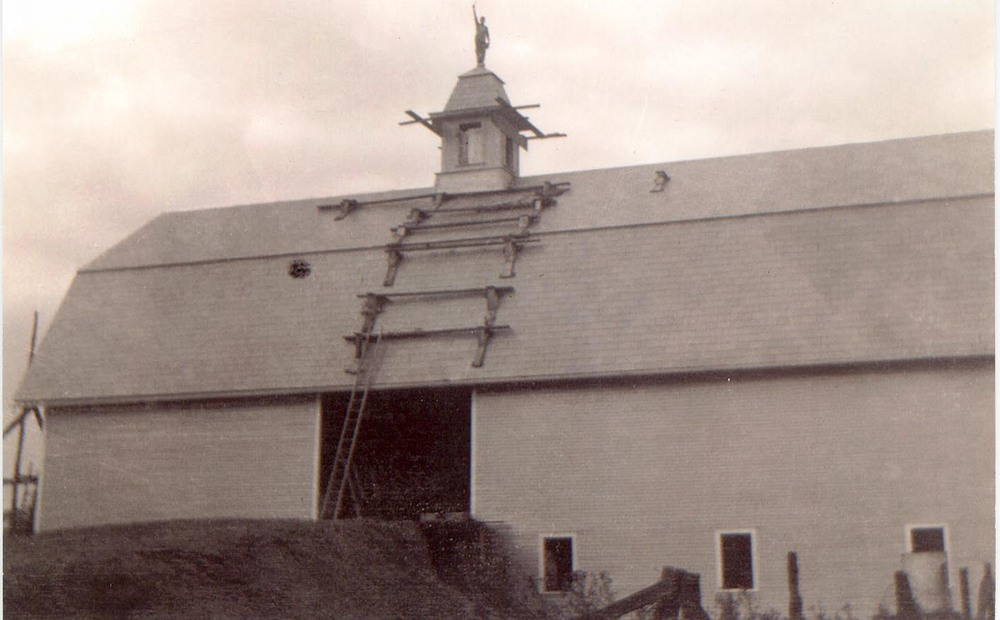 The barn burned to the ground in April, and by August, it was rebuilt. Record time!  Here, a worker stands victoriously atop the cupola - brave, but not wise!