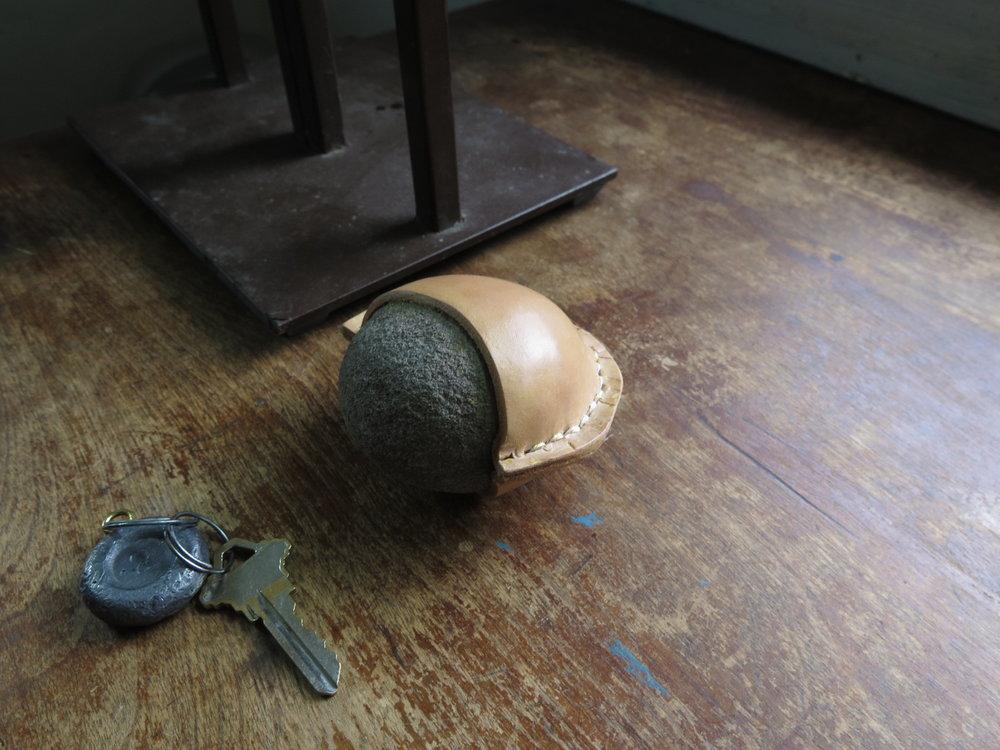 handmade saddle-stitched leather wrapped rock, hudson, ny