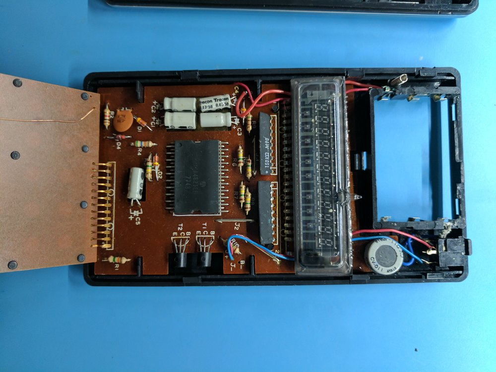 The insides. In the center is the A4821, date code 48th week of 1977. The VFD is toward the right, and the round-looking thing next to it is actually a DC-to-DC converter to provide -14.5v to the chip, and -31v to the VFD. The PCB on the left is the keyboard.