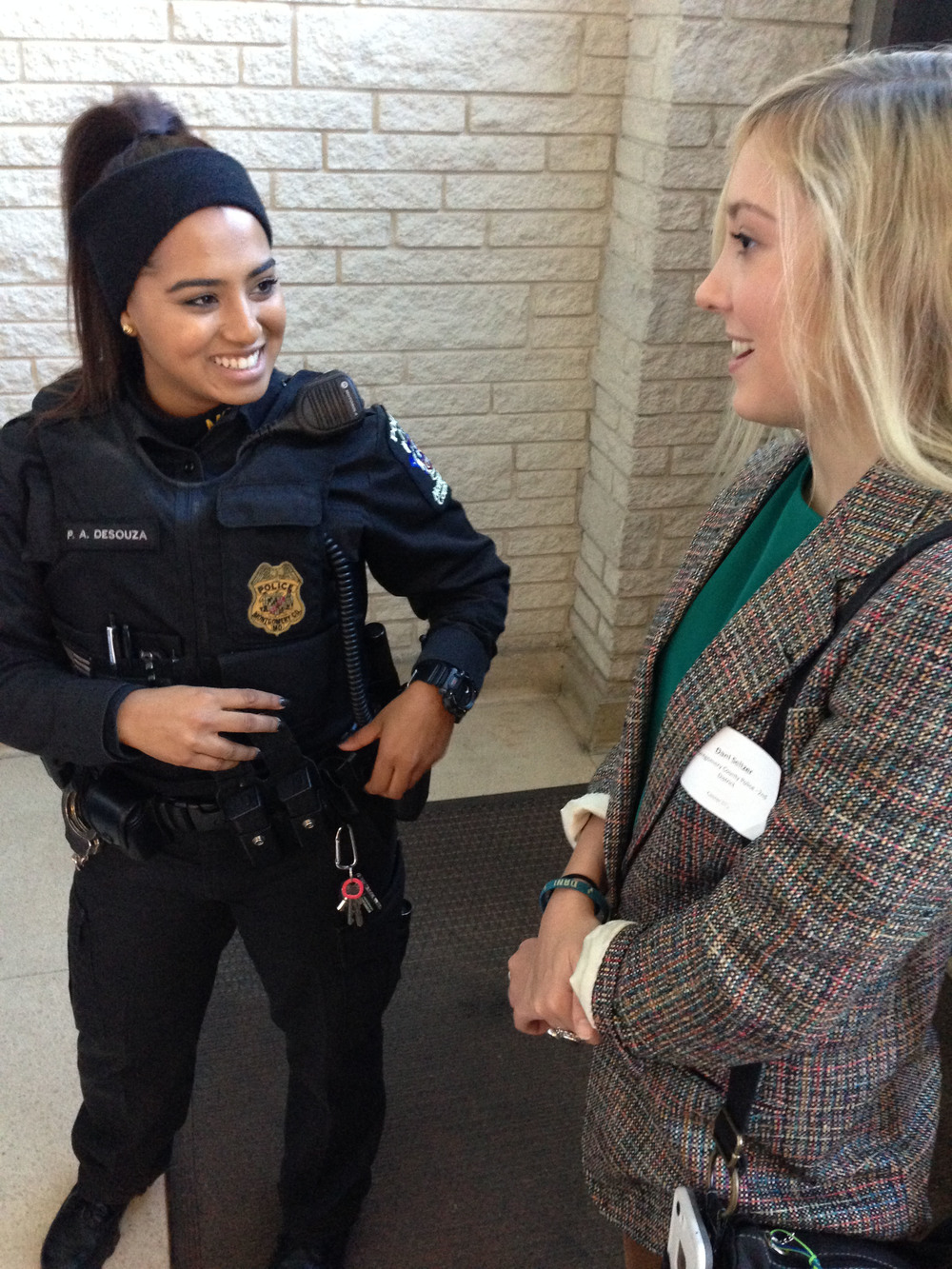 Montgomery County Officer Patty Desouza shows her bulletproof vest and other standard gear to Dani Seltzer, 17, a Bethesda-Chevy Chase High School student. Dani was meeting police as part of the school's job shadow day. (Bettina Lanyi/FOR THE WASHINGTON POST)