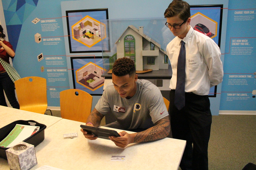 Wesley Shoemaker leads Washington Redskins rookie Su'a Cravens through the JA Finance Park® budgeting simulation.
