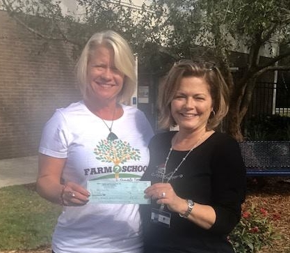 Elizabeth Leib, TTF2S Director, presents a $1000 check from Green Apple Day Reading garden sponsors Tampa International Airport, Tampa Bay Trane and the Phoenix Agency to Sherri Black, Cork Elementary Principal, January 2018