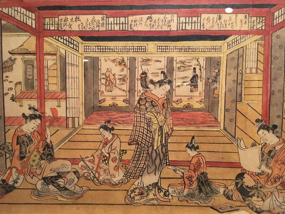 "Image portraying an elegant wakashu prostitute (prostitutes could be identified because they wore their ""obi"" or belt on the front). From the exhibition description panel: ""The depiction of the wakashu in larger scale than the young women reading and playing music suggests that, among them, he is the most desirable to the brothel's clients"""