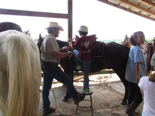 Larry McMillan helping customer onto horse
