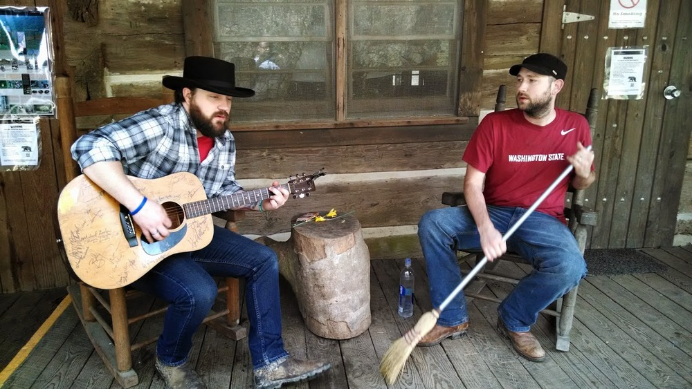 Playing music on front porch of Charit Creek Lodge with acoustic guitar and broom percussion
