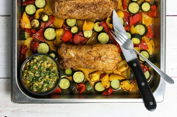 Pork tenderloin sheet pan bake with courgettes, peppers and olive salsa
