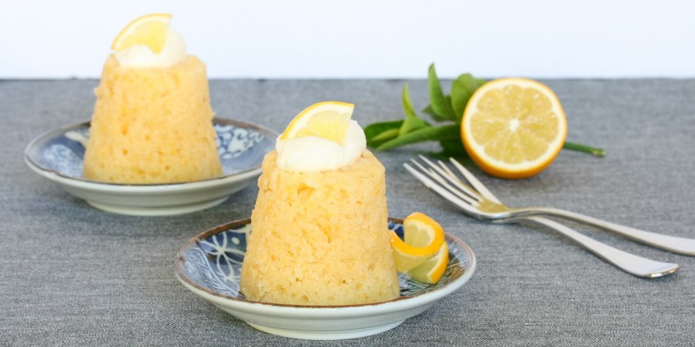 Mini steamed lemon puddings served with thick cream and lemon slices on blue patterned plates