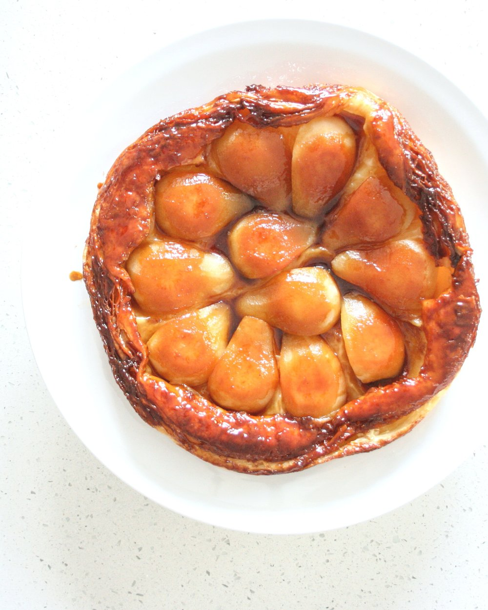 Apple tarte tatin, cooked in the steam oven and present whole on a white plate