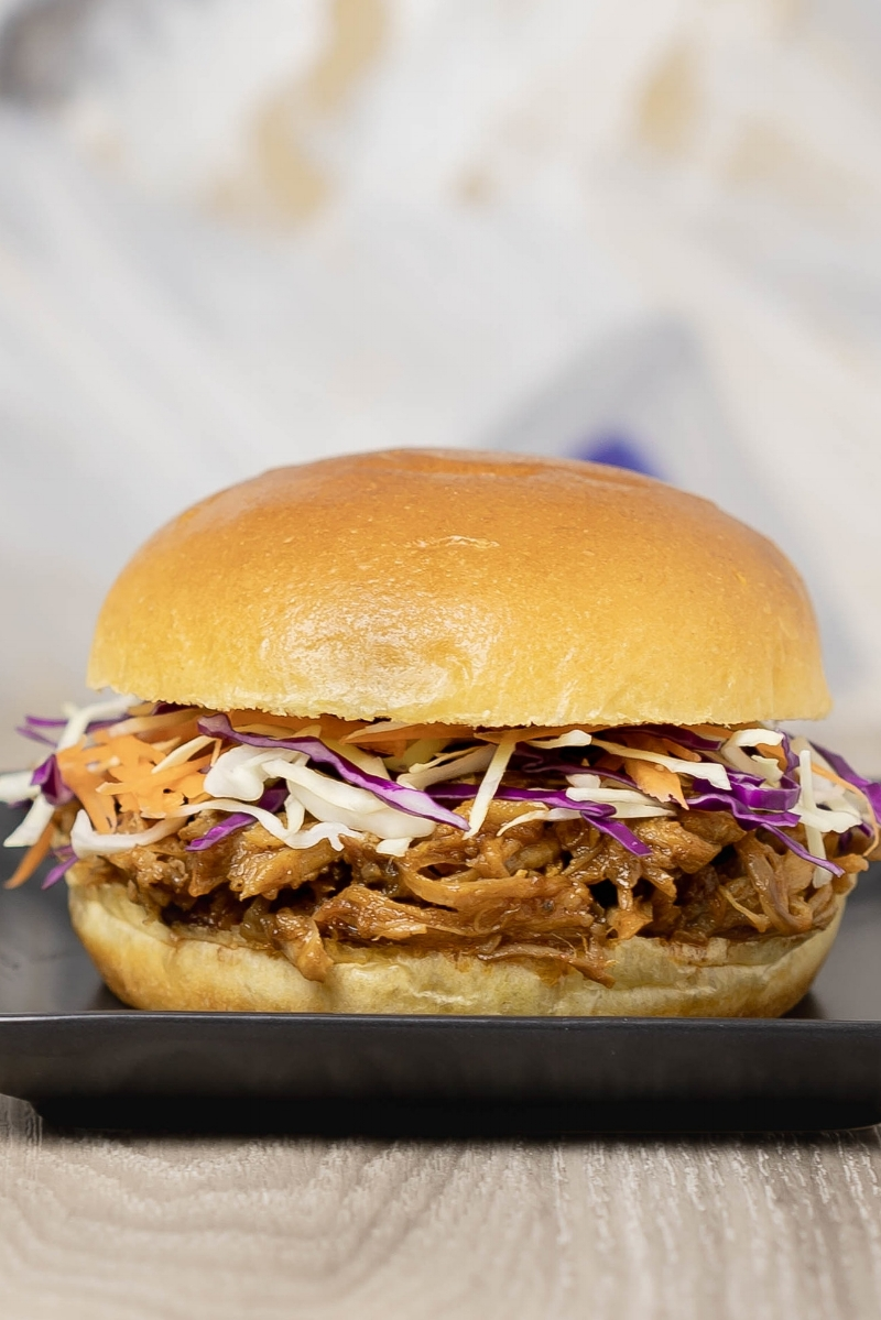 A brioche bun filled with steam oven pulled pork and coleslaw, on a square black dish.