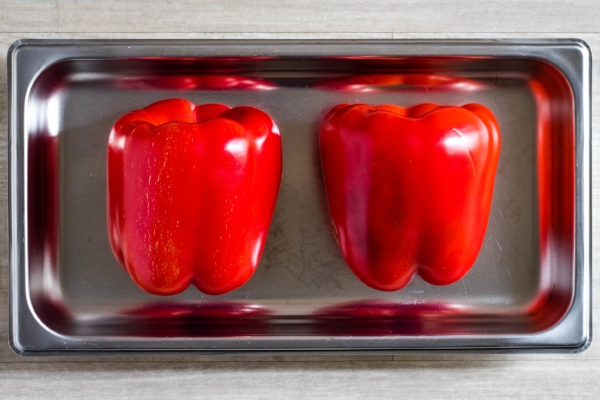 Two red bell peppers in a stainless steel oven tray, ready for roasting